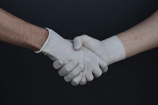 Händedruck mit Handschuhen: In der Coronakrise greifen viele Therapeuten auf digitale Möglichkeiten zurück.