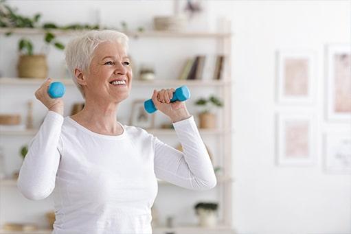 Eine ältere Dame mit kurzem grauem Haar und weißem Oberteil lächelt, während sie eine Physiotherapie Übung mit kleinen Hanteln durchführt.