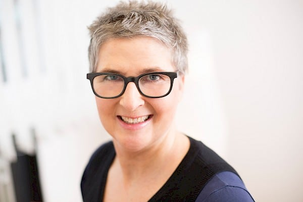 Woman with short hair and black glasses smiles at camera