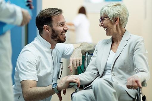 Junger Arzt in der Hocke neben einer älteren Patientin im Rollstuhl. Beide sehen sehr glücklich aus und strahlen.